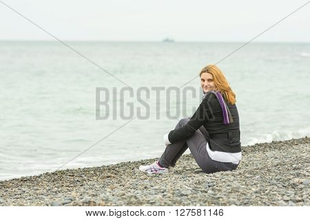 Smiling Young Girl Sitting On A Pebble Beach By The Sea On A Cloudy Cold Day Embracing Knees
