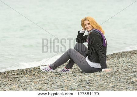 Young Girl With A Smile Sits On A Pebble Beach By The Sea On A Cloudy Cold Day