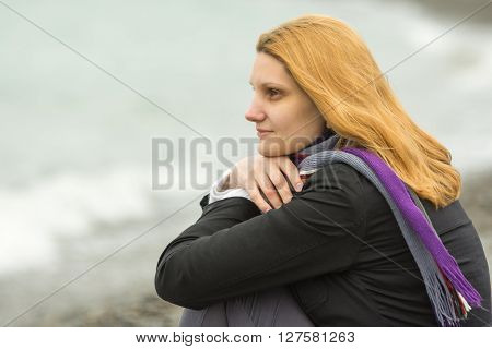 Portrait Of Enigmatic Smiling Girl On The Background Of The Surf On A Cloudy Cold Day