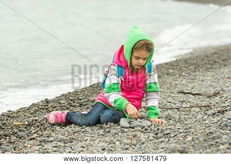 Seven-year Girl Sitting On A Pebble Beach In The Warm Clothing And With Enthusiasm Plays With Stones
