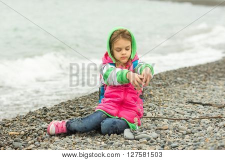 Seven-year Girl Sitting On A Pebble Beach In The Warm Clothing And Pours Out Through Her Fingers Sma