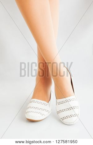 beautiful legs in a comfortable elegant shoes on a white background