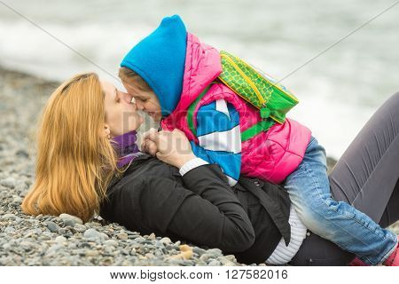 Young Mother Lying On The Pebbly Seashore Kissing The Nose Her Daughter Sitting On Her Riding