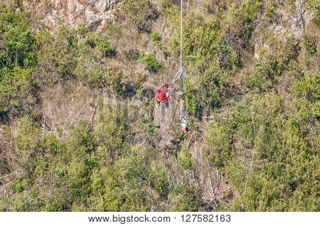 BLOUKRANS BRIDGE SOUTH AFRICA - MARCH 2 2016: An official preparing to hoist an unidentified bungee jumper back to the bridge after the worlds highest commercial bungee jump at the Bloukrans Bridge