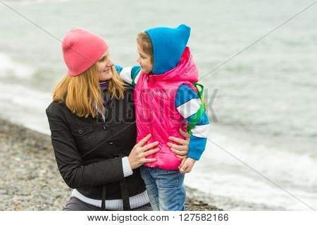 Mother Hugging Little Daughter And Tenderly Looking At Her On The Beach In Cold Weather