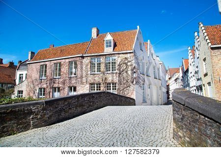View across the bridge at colorful traditional houses against blue sky in popular belgian destination Brugge, Belguim