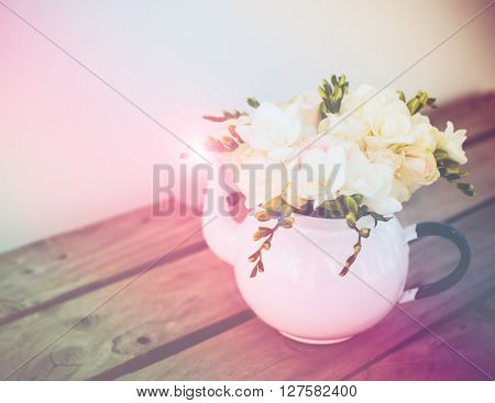 Lovely fresh bouquet of white summer roses and freesias in vintage enamel tea pot on an old brown wooden board. Retro style interior decoration with copy space.