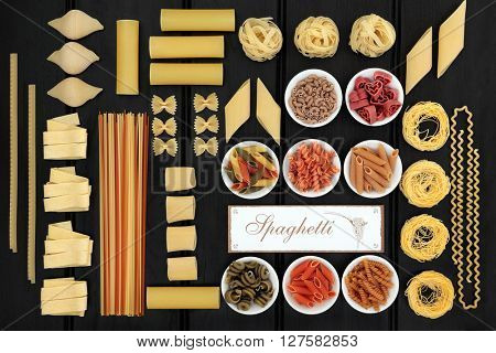 Italian dried food pasta selection with coloured varieties of spinach, beetroot and tomato with wooden spaghetti sign over dark wood background.