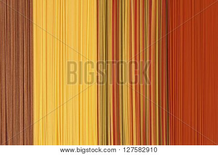 Coloured pasta spaghetti varieties of whole wheat, beetroot, spinach, carrot and tomato forming an abstract background.