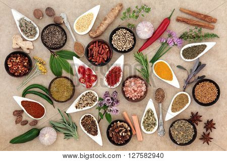Healthy herb and spice fresh and dried food seasoning over natural hemp paper background.