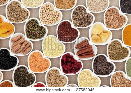 Dried health food in heart shaped bowls over hessian background. High in minerals, vitamins and antioxidants.