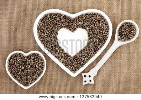 Hemp seed health food in heart shaped porcelain bowls and spoon over hessian background.
