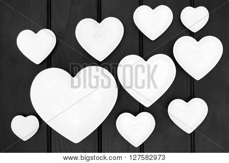 Porcelain heart shaped dishes over dark wood background.