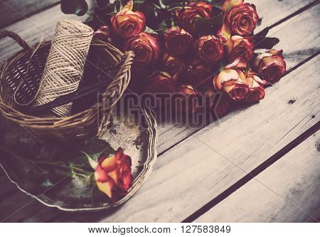 Floristic background, a bouquet of roses, scissors and twine in a basket on an old vintage wooden board.