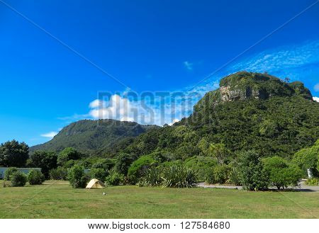 A tent in a campsite surround by trees and a hill