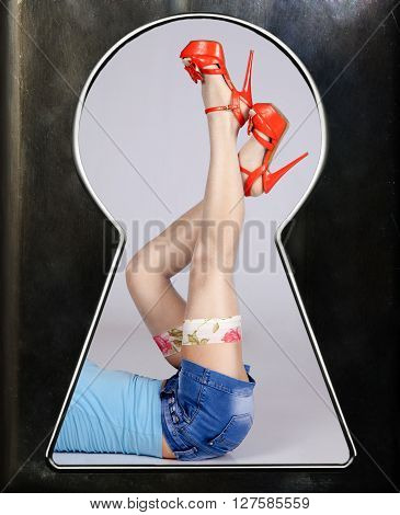 female legs in white stockings and red shoes with denim blue shorts as through a keyhole