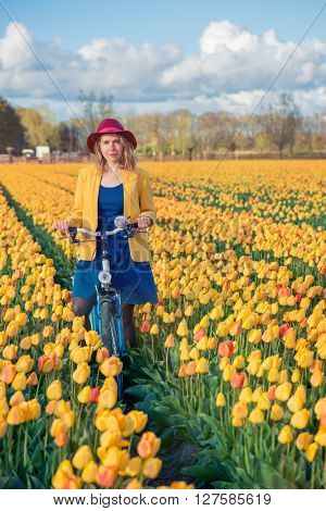 Smiling young woman cycling in a yellow tulips spring field on a sunny day