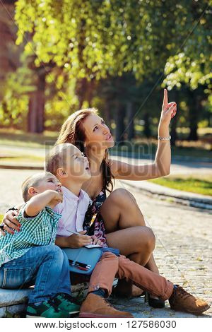 Young mother sitting with her children in the park, showing them something above with finger, they are looking with interest.