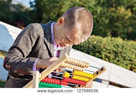 Back to school one little boy counting and playing on wooden abacus in the park.