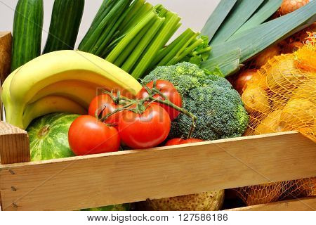 Fresh fruits and vegetables in a wooden box