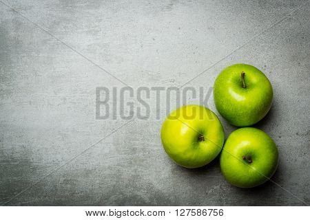 Three green apples on a concrete background