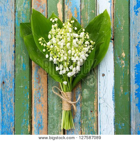 bouquet of lilies of the valley flowers with green leaves tied with twine in water droplets on wooden boards with remnants of old paint