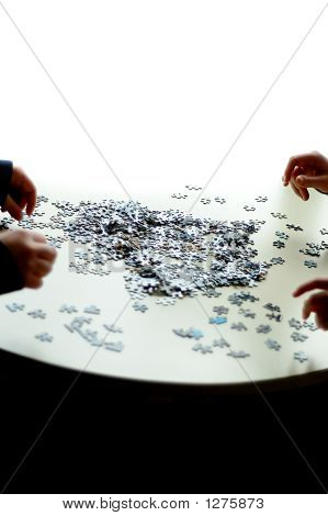 4 Hands Doing A Puzzle