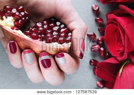 Skin care of a beauty female hand with grey pink and red asymmetry nail art manicure. And pockmarked grey background with red roses and pomegranat's seeds