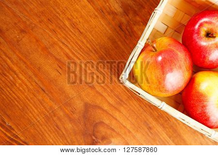 Fresh Red Apples In Basket Over Wooden Background.  Free Space For Text . Top View