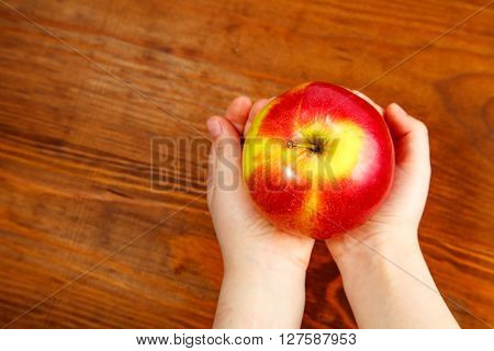 Child Holding An Apple In A Handful. Top View