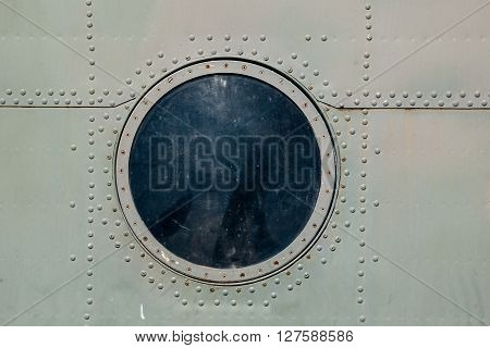 hatch window of the old aircraft riveted iron plates