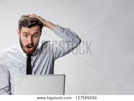 The young surprised man with his laptop computer on gray background