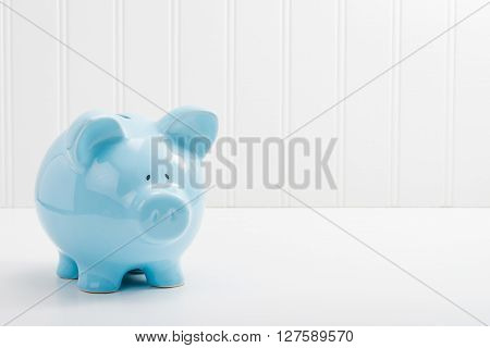 Blue porcelain piggybank with ample copy space.