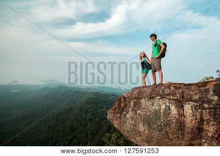 Couple in love standing on the mountain with backpacks and holding hands