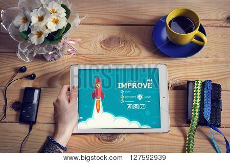 Laptop computer tablet pc and Improve design concept on wooden office desk with copy space. Improve design concept background with rocket.