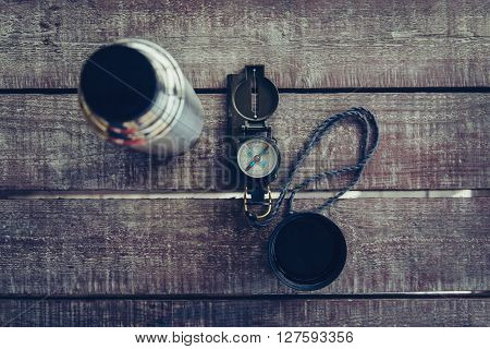 Travel compass and thermos on wooden table top view