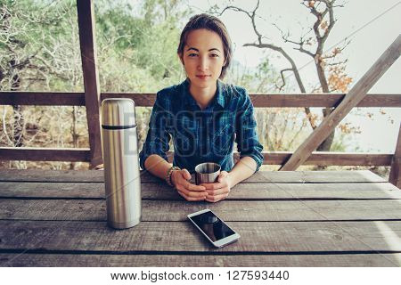 Young woman resting in wooden veranda in summer outdoor looking at camera. Girl has a picnic in arbor