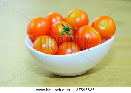 Small tomatoes of sherry kind in a small white bowl.