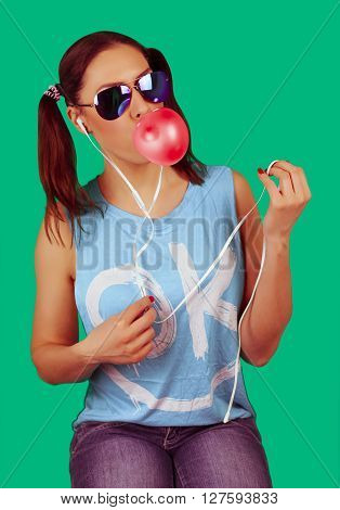 Beautiful funny model girl wearing sunglasses with bubble of chewing gum listens to the music (white earphones)