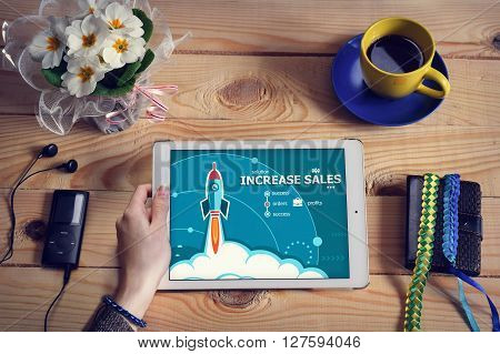 Laptop computer tablet pc and Increase sales design concept on wooden office desk with copy space. Increase sales design concept background with rocket.