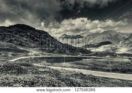 Beautiful curvy road passing through Jelepla Pass Dzuluk Sikkim India -with blue sky and clouds in the background. Black and white image