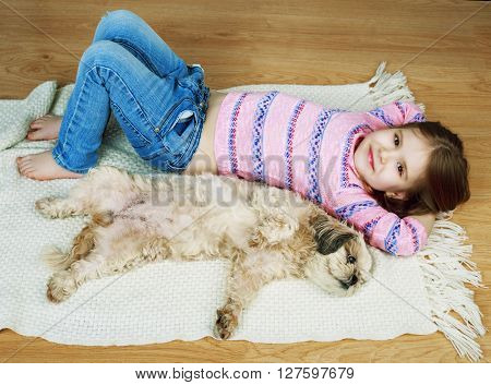 happy girl with her dog on the floor at home