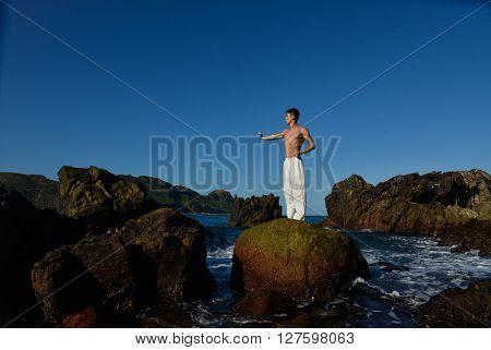 Full body muscular Yoga man in the morning at beach