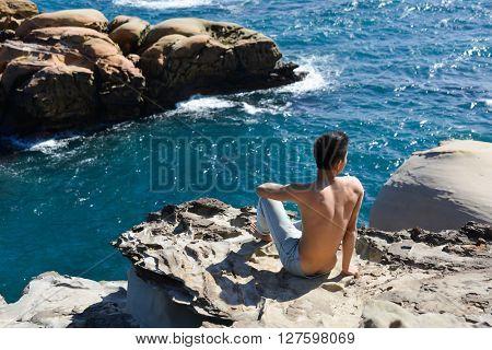 Sport man back on rocks at beach