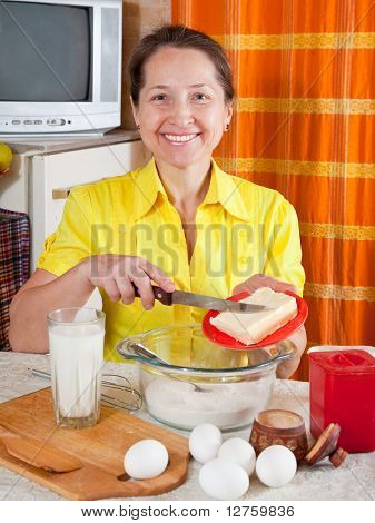 Frau fügt Teig Margarine