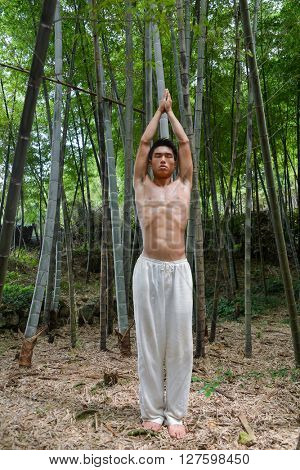 Full portrait of muscular young man doing yoga exercise over forest,