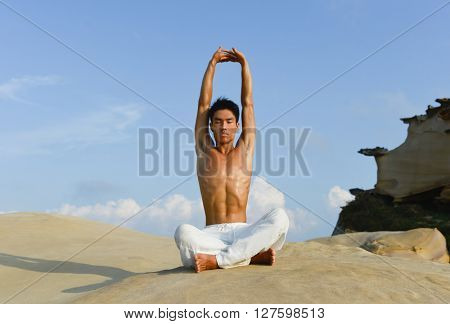 Full body handsome man doing yoga exercise in outdoors