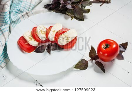 Italian tomato and mozzarella Caprese salad seasoned with pepper and salt and garnished with leaves of fresh basil on a white plate.