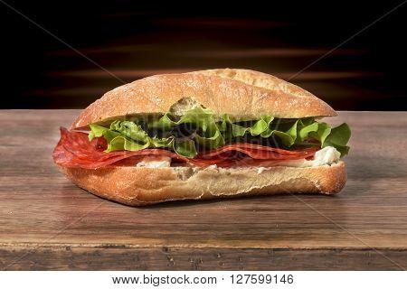 sandwich salami, gorgonzola and salad on wood
