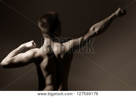 Muscular man shows back. Athletic man on a dark background